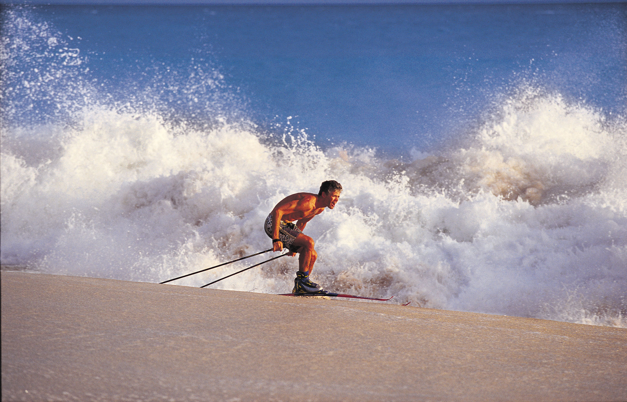 man apline skiing on a sandy beach with a large wave breaking behind him