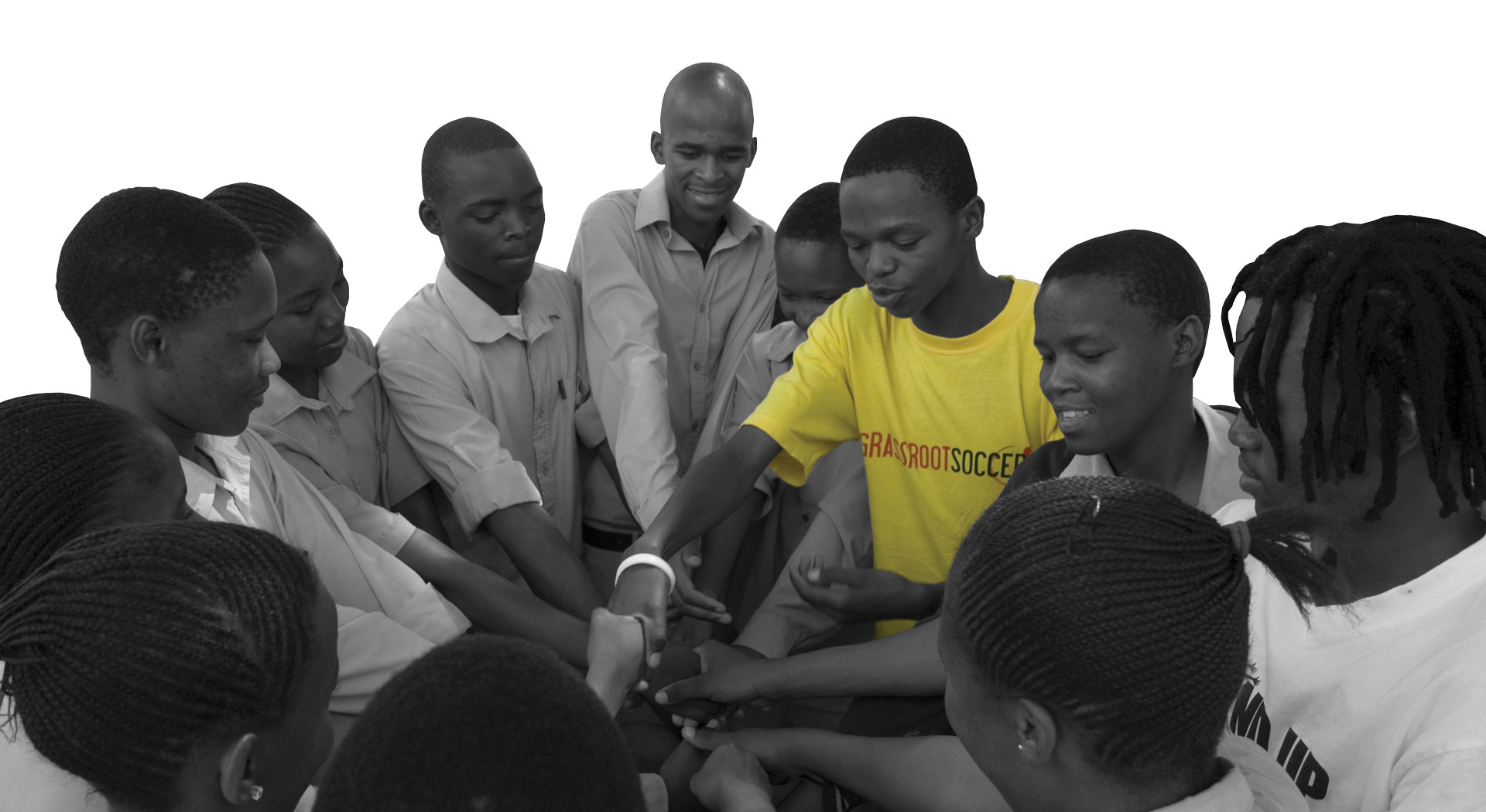 group of man and teenage boys in a circle with hands in the middle