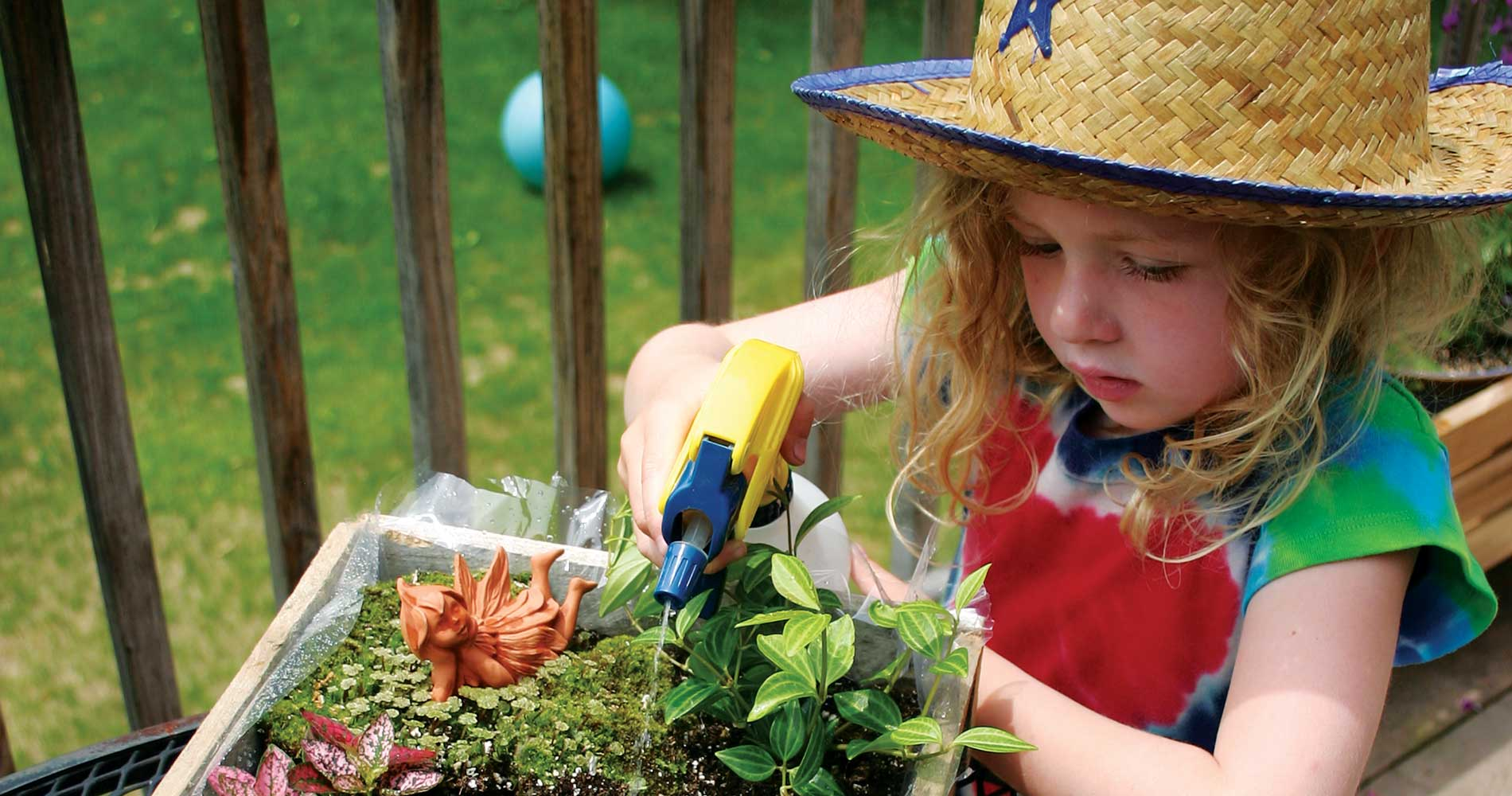 young blonde girl with a straw hat watering a small garden with a squirt bottle