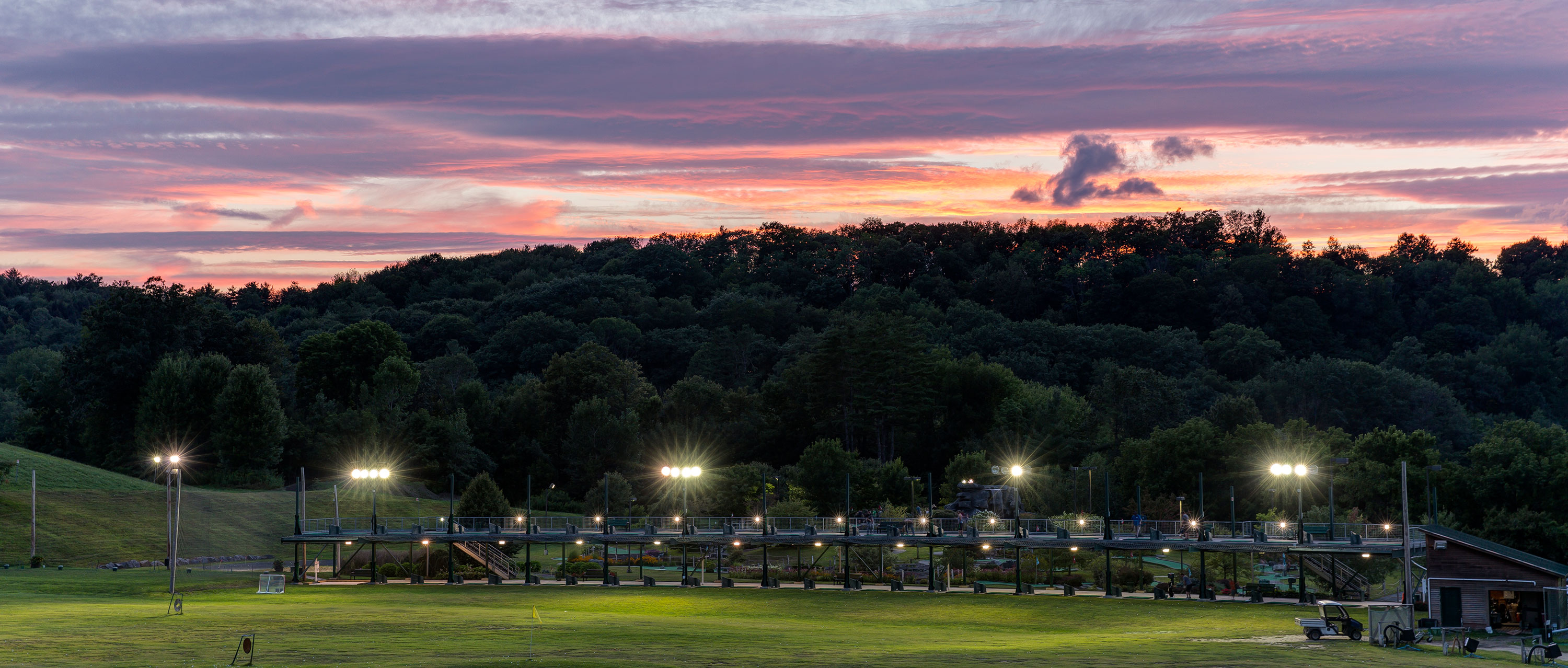 a golf green at sunset, lit by floodlights